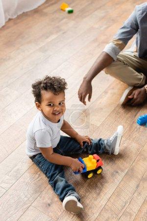 Photo pour Vue recadrée de l'homme afro-américain près de son fils jouant avec camion jouet sur le sol - image libre de droit