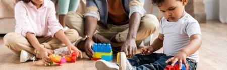 Photo pour Vue recadrée du père afro-américain avec des enfants jouant avec des blocs de construction sur le sol, vue panoramique - image libre de droit