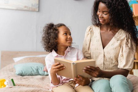 Photo for African american mom and child looking at each other while reading book together - Royalty Free Image