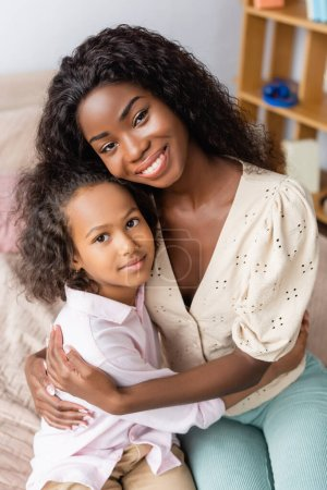Photo for African american mother and child looking at camera while hugging at home - Royalty Free Image