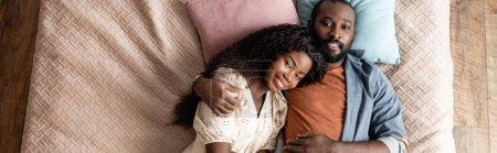 Foto de Vista superior del hombre afroamericano abrazando a la esposa mientras está acostado en la cama y mirando a la cámara, imagen horizontal - Imagen libre de derechos