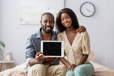Photo for Young african american man holding digital tablet with blank screen near wife in bedroom - Royalty Free Image