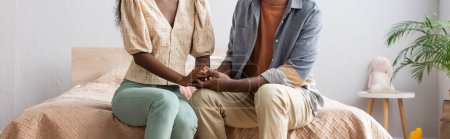 Photo for Cropped view of african american couple in casual clothes sitting on bed and holding hands, horizontal image - Royalty Free Image