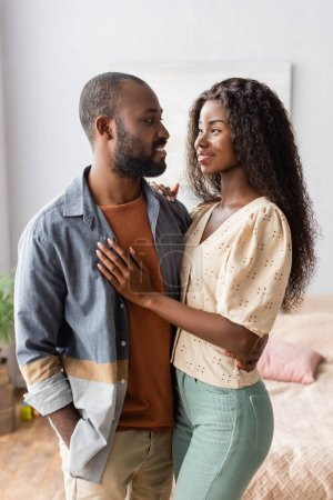 young african american woman in blouse touching husband standing with hand in pocket