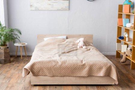 Photo pour Chambre spacieuse, lit avec couverture beige, étagère avec livres et plantes décoratives en pot de fleurs - image libre de droit