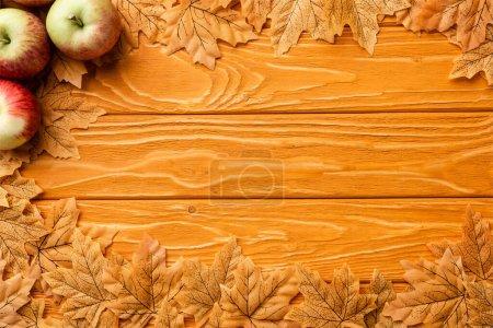 Photo pour Top view of ripe apples and autumnal foliage on wooden background - image libre de droit