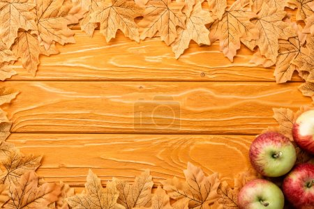 top view of ripe apples and autumnal foliage on wooden background