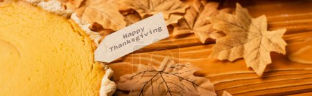 Photo for Thanksgiving pumpkin pie with autumnal foliage on wooden background, panoramic shot - Royalty Free Image