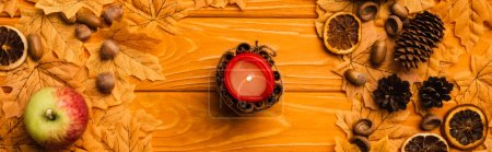 top view of burning candle with autumnal decoration on wooden background