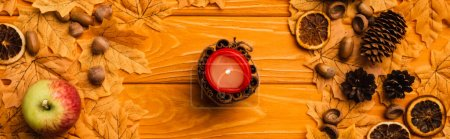 Photo for Top view of burning candle with autumnal decoration on wooden background - Royalty Free Image