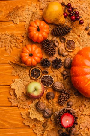 Photo pour Top view of burning candle with autumnal decoration on wooden background - image libre de droit