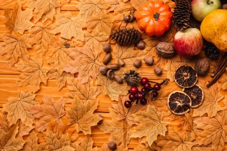 Photo for Top view of autumnal decoration and food on golden foliage on wooden background - Royalty Free Image