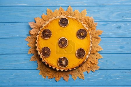 top view of decorated pumpkin pie with golden foliage on blue wooden background