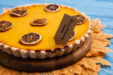 close up view of decorated pumpkin pie with happy thanksgiving card