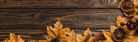 Photo for Top view of autumnal decoration and foliage on brown wooden background, panoramic shot - Royalty Free Image