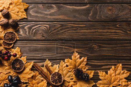 Photo for Top view of autumnal decoration and foliage on brown wooden background - Royalty Free Image