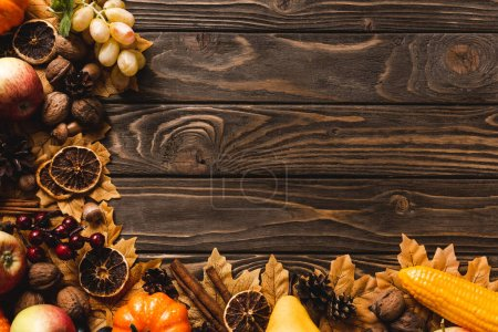 Photo for Top view of autumnal harvest and foliage on brown wooden background - Royalty Free Image