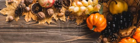 Photo for Top view of autumnal harvest on foliage on brown wooden background, panoramic shot - Royalty Free Image