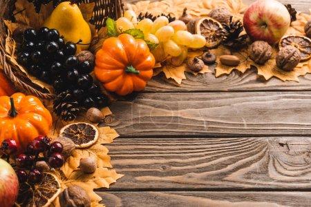 Photo pour Autumnal harvest in basket on foliage on brown wooden background - image libre de droit