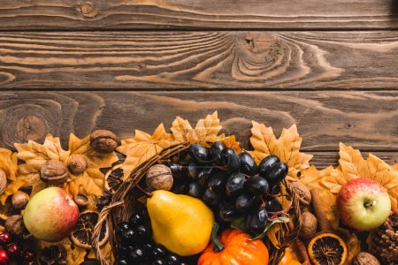 top view of autumnal harvest in basket on foliage on brown wooden background