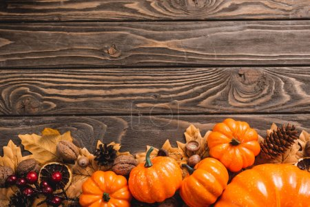 top view of autumnal decoration and pumpkins on brown wooden background