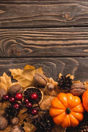 Photo pour Top view of autumnal decoration and pumpkin on brown wooden background - image libre de droit