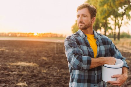 rancher in plaid shirt holding bucket while standing on plowed field in sunshine