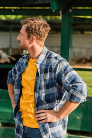 farmer in plaid shirt looking away while standing with hands on hips