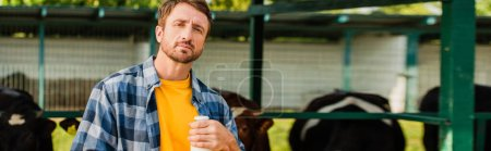 Photo for Horizontal concept of rancher in plaid shirt with bottle of fresh milk near cowshed - Royalty Free Image