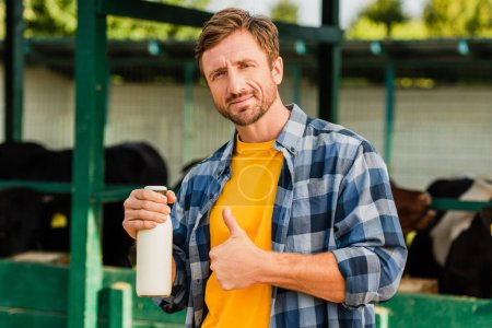 Photo for Farmer in plaid shirt showing thumb up while holding bottle of fresh milk on farm - Royalty Free Image