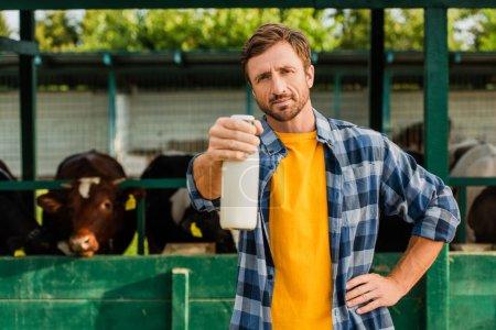 Foto de Ranchero en camisa a cuadros de pie cerca de establo con la mano en la cadera y mostrando botella de leche fresca - Imagen libre de derechos