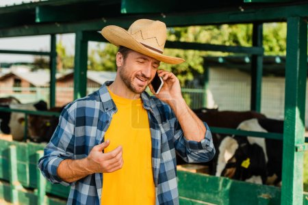 Photo for Farmer in straw hat and checkered shirt talking on smartphone near cowshed on farm - Royalty Free Image