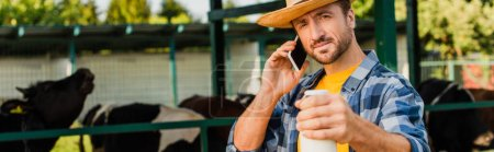 Photo for Panoramic concept of farmer in straw hat and plaid shirt holding bottle of milk while talking on mobile phone - Royalty Free Image