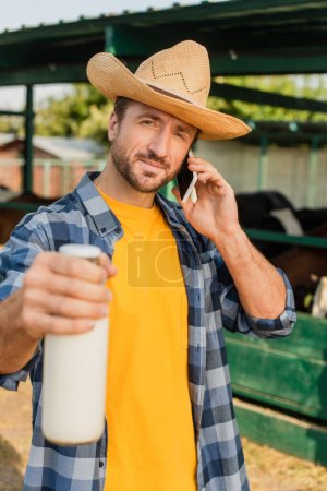 Photo for Selective focus of rancher in straw hat and checkered shirt talking on smartphone while showing bottle of milk - Royalty Free Image