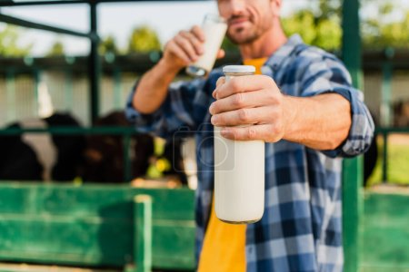 Photo for Selective focus of farmer in checkered shirt holding bottle and glass of fresh milk - Royalty Free Image