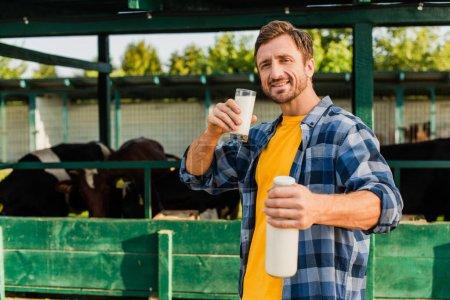 Photo pour Foyer sélectif de l'agriculteur en chemise à carreaux tenant le verre et bouteille de lait frais près étable - image libre de droit