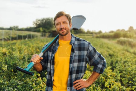 Photo for Farmer in plaid shirt looking at camera while holding shovel in field - Royalty Free Image