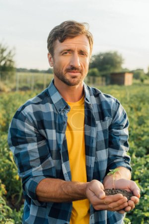 Photo for Farmer in plaid shirt holding green sprout in cupped hands while looking at camera - Royalty Free Image