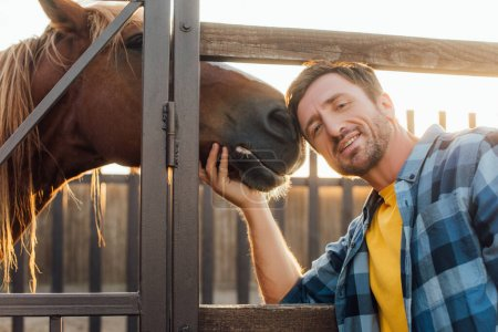 rancher in plaid shirt touching horse while looking at camera near corral fence