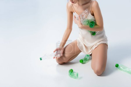 cropped view of woman in silk dress collecting plastic bottles on white, ecology concept