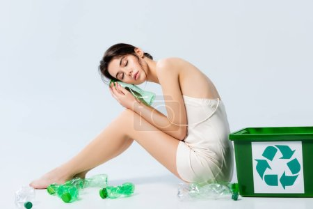 Photo for Brunette woman with closed eyes in silk dress sitting near plastic bottles and trash bin with recycle sign on white, ecology concept - Royalty Free Image