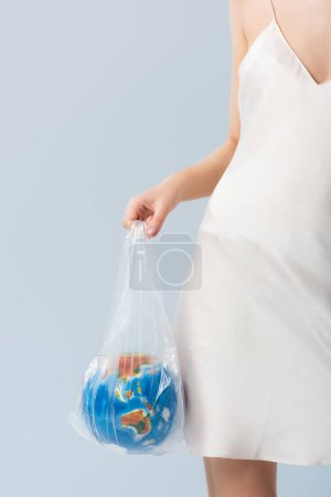 cropped view of woman in silk dress holding plastic bag with globe isolated on grey, ecology concept