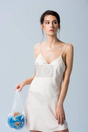 Photo pour Femme brune en robe de soie tenant sac plastique avec globe isolé sur gris, concept écologie - image libre de droit