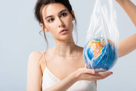 Photo for Young woman in silk dress holding plastic bag with globe isolated on white, ecology concept - Royalty Free Image