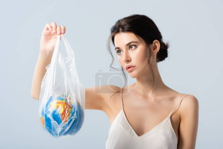 Photo pour Jeune femme en robe de soie regardant sac en plastique avec globe isolé sur blanc, concept d'écologie - image libre de droit