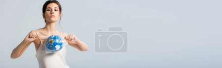 horizontal image of young woman holding plastic bag with globe and looking at camera isolated on grey, ecology concept