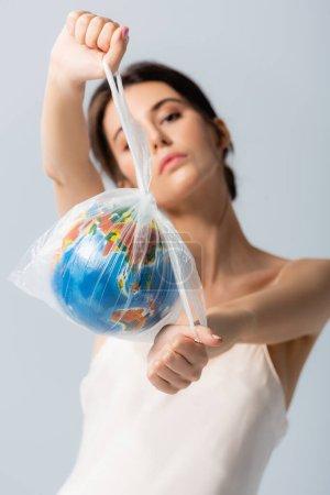 enfoque selectivo de la mujer joven sosteniendo bolsa de plástico con globo y mirando a la cámara aislada en blanco, concepto de ecología
