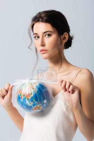 joven morena mujer sosteniendo bolsa de plástico con globo y mirando a la cámara aislada en blanco, concepto de ecología