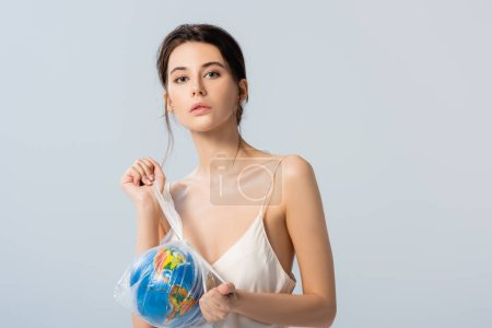 Photo for Brunette model holding plastic bag with globe and looking at camera isolated on white, ecology concept - Royalty Free Image