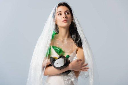 mujer joven con bolsa de plástico en la cabeza de pie en vestido de seda con botellas vacías aisladas en gris, concepto de ecología